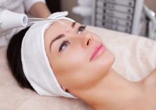 The cosmetologist makes the procedure electrotherapy  of the facial skin. Of a beautiful, young woman in a beauty salon.Cosmetology and professional skin care Stock Image