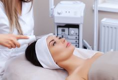 The cosmetologist makes the procedure Microcurrent therapy of the facial skin of a beautiful, young woman Stock Image