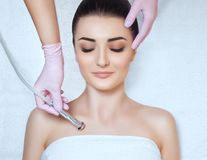 The cosmetologist makes the procedure Microdermabrasion of the décolletage skin of a beautiful, young woman. In a beauty salon.Cosmetology and professional Stock Photo
