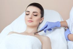 The cosmetologist makes the procedure Microdermabrasion of the décolletage skin. Of a beautiful, young woman in a beauty salon.Cosmetology and professional Royalty Free Stock Photos