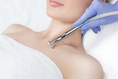 The cosmetologist makes the procedure Microdermabrasion of the décolletage skin. Of a beautiful, young woman in a beauty salon.Cosmetology and professional Stock Image