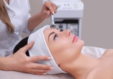 The cosmetologist makes the procedure Microdermabrasion of the facial skin of a beautiful, young woman in a beauty salon. Cosmetology and professional skin care Royalty Free Stock Images