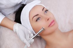 The cosmetologist makes the procedure Microdermabrasion of the facial skin of a beautiful, young woman in a beauty salon. Cosmetology and professional skin care Royalty Free Stock Image