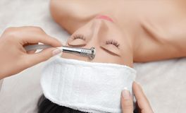 The cosmetologist makes the procedure Microdermabrasion of the facial skin of a beautiful, young woman in a beauty salon. Cosmetology and professional skin care Stock Photo