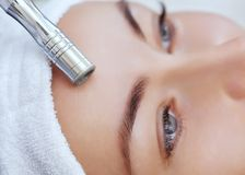 The cosmetologist makes the procedure Microdermabrasion of the facial skin of a beautiful, young woman in a beauty salon. Royalty Free Stock Images
