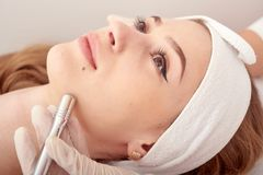 The cosmetologist makes the procedure Microdermabrasion of the facial skin of a beautiful, young woman in a beauty salon royalty free stock image