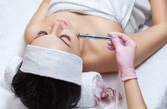 The cosmetologist makes the procedure Microdermabrasion of the facial skin of a beautiful, young woman. In a beauty salon.Cosmetology and professional skin care Stock Photo