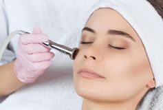 The cosmetologist makes the procedure Microdermabrasion of the facial skin of a beautiful, young woman. In a beauty salon.Cosmetology and professional skin care Stock Photos
