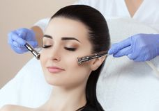 The cosmetologist makes the procedure Microdermabrasion of the facial skin of a beautiful, young woman. In a beauty salon.Cosmetology and professional skin care Stock Images