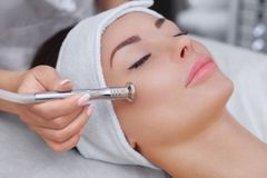The cosmetologist makes the procedure Microdermabrasion of the facial skin. Of a beautiful, young woman in a beauty salon.Cosmetology and professional skin care stock photo