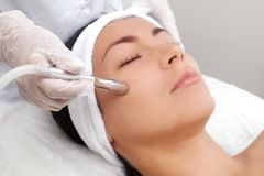 The cosmetologist makes the procedure Microdermabrasion of the facial skin. Of a beautiful, young woman in a beauty salon.Cosmetology and professional skin care stock images