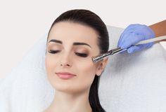 The cosmetologist makes the procedure Microdermabrasion of the facial skin. Of a beautiful, young woman in a beauty salon.Cosmetology and professional skin care Royalty Free Stock Image