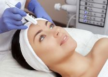 The cosmetologist makes the procedure treatment of Couperose of the facial skin of a beautiful, young woman in a beauty salon. stock image
