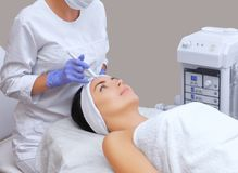 The cosmetologist makes the procedure treatment of Couperose of the facial skin of a beautiful, young woman in a beauty salon. The cosmetologist makes the Stock Photos