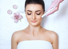 The cosmetologist makes the procedure treatment of Couperose of the facial skin. Of a beautiful, young woman in a beauty salon.Cosmetology and professional skin Stock Photography