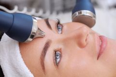 The cosmetologist makes the procedure an ultrasonic cleaning of the facial skin. Of a beautiful, young woman in a beauty salon.Cosmetology and professional skin stock photos