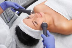 The cosmetologist makes the procedure an ultrasonic cleaning of the facial skin of a beautiful, young woman in a beauty salon. Royalty Free Stock Photography
