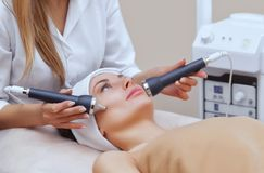 The cosmetologist makes the procedure an ultrasonic cleaning of the facial skin of a beautiful, young woman. In a beauty salon.Cosmetology and professional skin Royalty Free Stock Photography