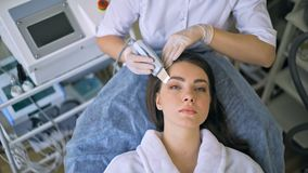 The cosmetologist makes the procedure ultrasonic face peeling of the facial skin of a beautiful, young woman in a beauty. Salon stock video