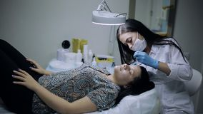 Professional Cosmetologist makes eyebrow correction in a girl with problem skin on her face stock footage
