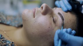 Professional Cosmetologist makes eyebrow correction in a girl with problem skin on her face stock video footage