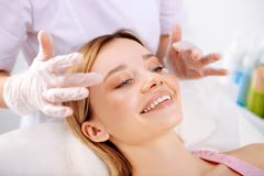 Cosmetologist making face massage of beautiful smiling client. Face massage. Cosmetologist making face massage of beautiful smiling client feeling satisfied stock photos