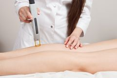Cosmetologist making laser epilation on the girl`s calf and thighs. Hair removal on legs. Apparatus cosmetology. Spa Stock Photography