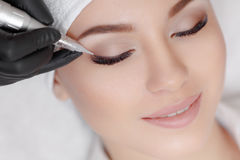 Cosmetologist making permanent make up at beauty salon. Close up of woman lying on couch at beauty salon with closed eyes and enjoying when cosmetologist making Stock Image