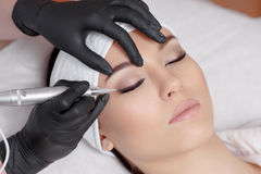 Cosmetologist making permanent makeup at beauty salon. Side view of cosmetologist wearing black gloves making permanent makeup for young beautiful woman. Using Stock Images