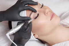 Cosmetologist making permanent makeup. Close up. Tattooist making permanent make-up. Attractive lady getting facial care and tattoo. Permanent make-up tattoo stock photography