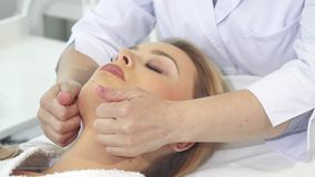 Cosmetologist massages client`s face royalty free stock image