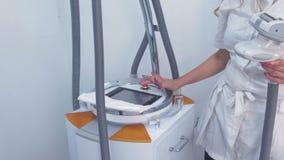 Cosmetologist nimmt auf und schließt den Apparat für lpg-Massage mit ein Vorbereitung für lpg-Massage Übergibt Nahaufnahme stock footage