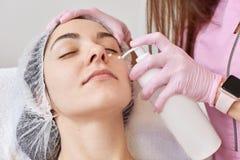 Cosmetologist past bevochtigend masker op vrouwelijk gezicht van grote witte fles toe Het jonge vrouw liggende ontspannen, met ge stock afbeeldingen