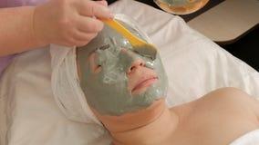 Cosmetologist past een grijs alginate masker op het meisjess gezicht en het linkeroog toe Aziatische vrouw op middelbare leeftijd royalty-vrije stock afbeelding