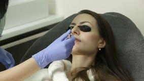 Cosmetologist past gel op gezicht van patiënt vóór epilationprocedure toe stock videobeelden