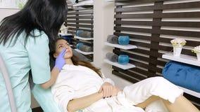 Cosmetologist past gel op gezicht van patiënt vóór epilationprocedure toe stock footage