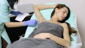 Cosmetologist past gel op oksels van patiënt toe vóór epilationprocedure stock video