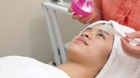 Cosmetologist past gezichtsmasker vrouwelijk gezicht toe stock afbeelding