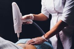 Cosmetologist with patient and professional tattoo removal laser in salon. Cosmetologist with patient and professional tattoo removal laser in salon royalty free stock image