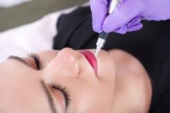 Cosmetologist permanent van toepassing zijn maakt omhoog op lippen op mooi jong meisje royalty-vrije stock foto