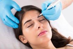 Cosmetologist permanent van toepassing zijn maakt omhoog op wenkbrauwen royalty-vrije stock afbeeldingen