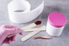 Cosmetologist in pink protective gloves holding stick with wax for depilation.Concept of preparation for waxing treatments royalty free stock photo