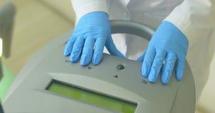 Cosmetologist préparant le dispositif d'epilation de laser au travail Commencez à fonctionner banque de vidéos