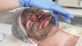 Cosmetologist preparing face of male client for carbon facial peeling. Handsome man getting skincare treatment by beautician. Man receiving facial carbon stock video footage