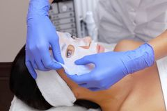 The cosmetologist for procedure of cleansing and moisturizing the skin, applying a sheet mask to the face of a young woman in beau Stock Photography