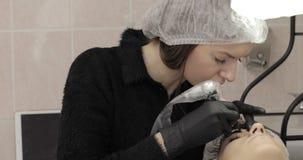 Cosmetologist profissional na veste preta que faz as testas permanentes vídeos de arquivo