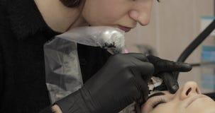 Cosmetologist profissional na veste preta que faz as testas permanentes filme