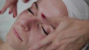 Cosmetologist profissional que faz a massagem facial na sala de estar de beleza filme