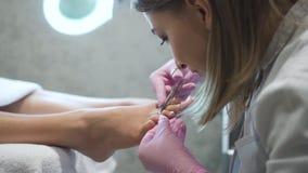 Cosmetologist profissional que faz o tratamento de mãos no barefeet fêmea vídeos de arquivo