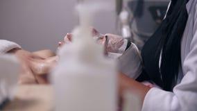 Cosmetologist profissional que guarda suas mãos na cara do ` s da mulher ao apllying a máscara especial na cara e no pescoço do ` video estoque